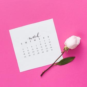 Flor rosa con calendario de marzo en mesa.