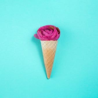 Flor rosa en cono de waffle en mesa