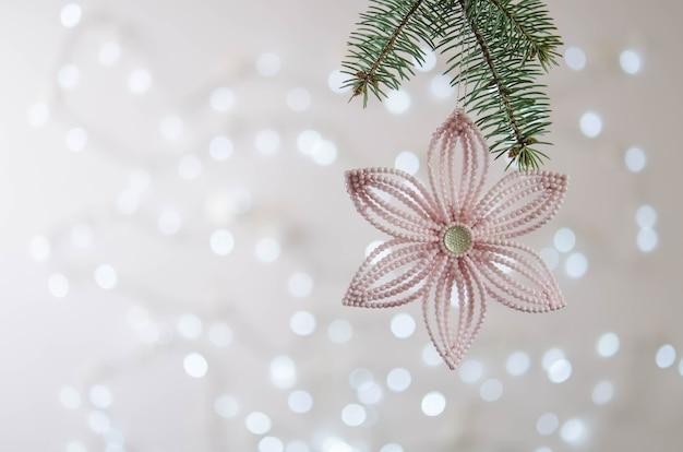 Flor rosa cuelga de la rama de un árbol de navidad. bokeh. decoración navideña