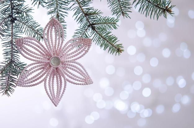 Flor rosa cuelga de la rama de un árbol de navidad