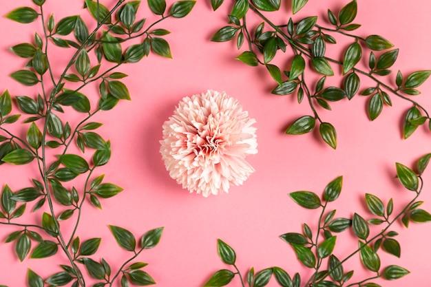 Flor rosa con marco de hojas