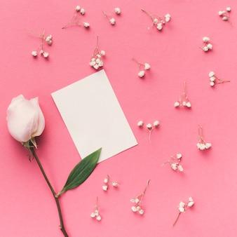 Flor rosa con pequeño papel sobre mesa.