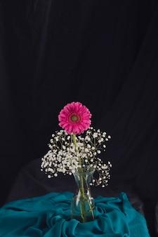 Flor rosa con ramitas de flores en un jarrón cerca de un textil azul en la oscuridad