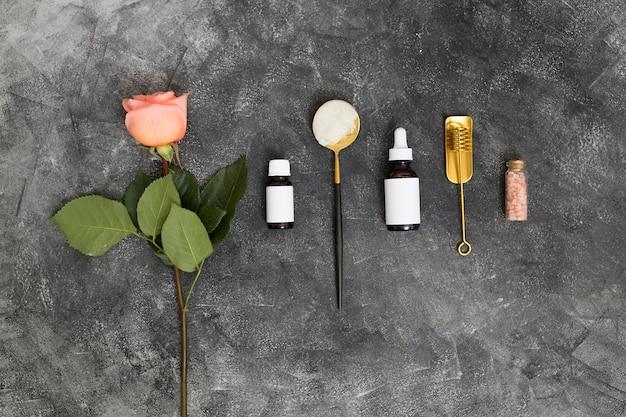 Flor rosa rosa; aceites esenciales y sal de roca del himalaya sobre fondo negro texturado.