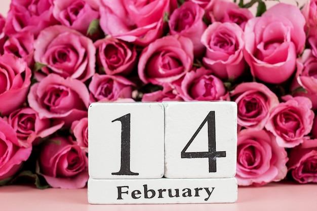 Flor rosa rosa y calendario 14 de febrero sobre fondo rosa. concepto de vacaciones de amor, romántico y feliz día de san valentín