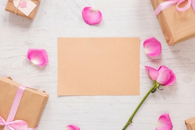 Flor rosa rosa con papel y cajas de regalo.