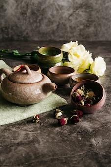 Flor de rosa seca con tetera; tazas de té y ramo de rosas sobre fondo de hormigón