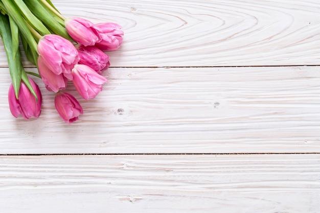 Flor rosada del tulipán en el fondo de madera
