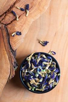La flor seca del guisante de mariposa del concepto de la comida para hace el té herbario en taza de cerámica en el tablero de madera