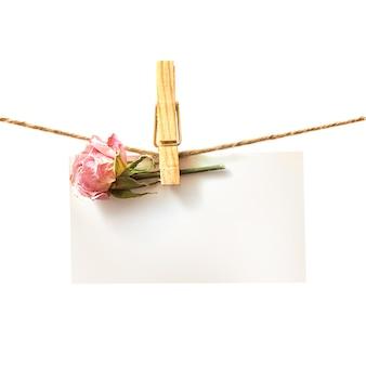 Flor y tarjeta blanca con ropa.