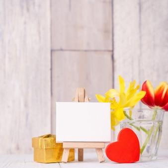 Flor de tulipán en florero de vidrio con decoración de marco de imagen en la pared de fondo de mesa de madera en casa, de cerca, concepto de diseño del día de la madre.