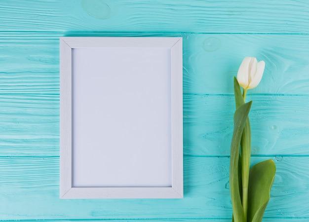 Flor de tulipán con marco en blanco en la mesa