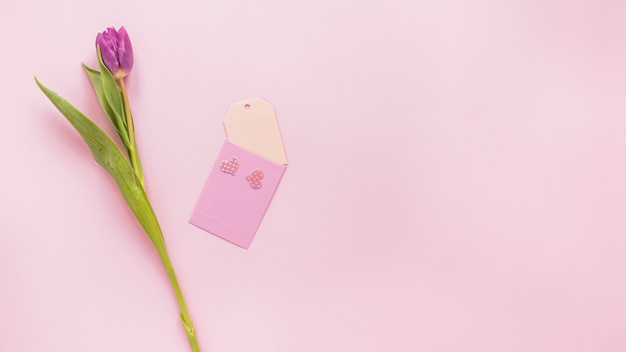 Flor de tulipán morado con papel pequeño en mesa