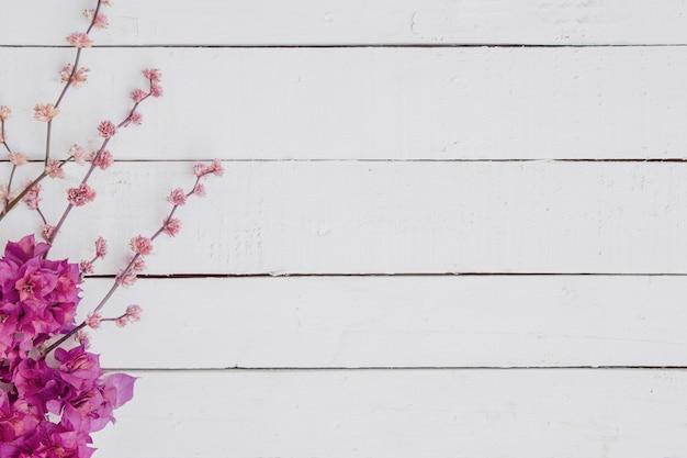 Floral de ramas sobre un fondo blanco de madera.