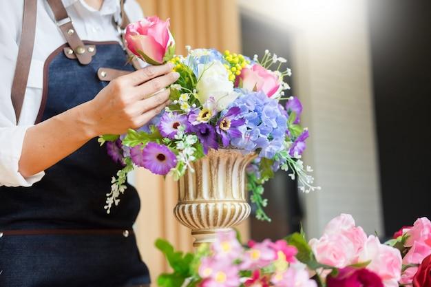 Floreria arreglando hermoso chaleco artificial en la tienda de flores