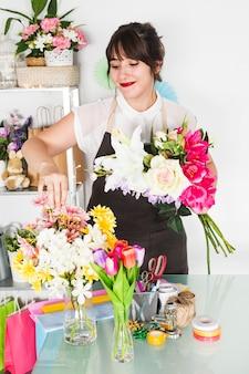 Floreria bonita mujer arreglando flores en florero