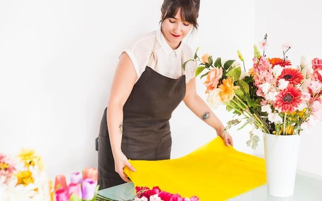 Floreria femenina arreglando tela amarilla para hacer ramo de flores.