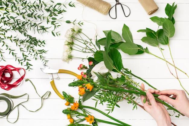 Floreria femenina haciendo hermoso ramo en florería