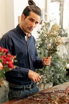 Floreria hombre en camisa cortando tallos de flores