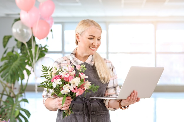 Floreria con laptop y hermoso ramo en tienda