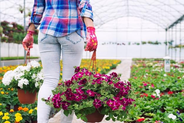 Floreria mujer irreconocible llevando macetas y flores en el vivero de plantas
