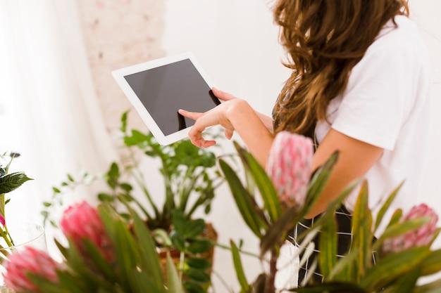 Floreria de primer plano escribiendo en una tableta