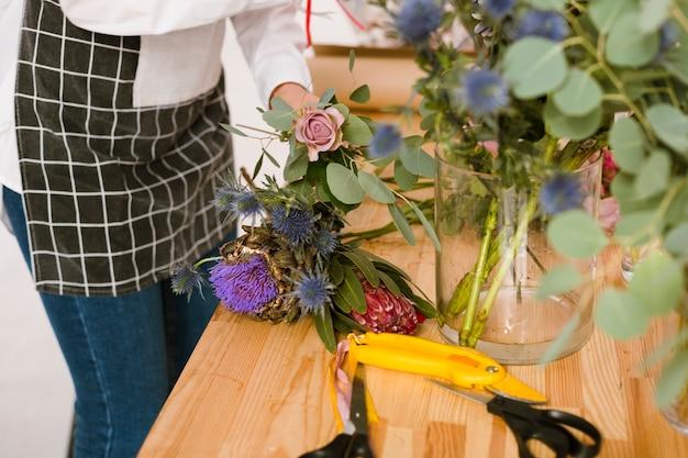 Floreria de primer plano trabajando en la tienda de flores