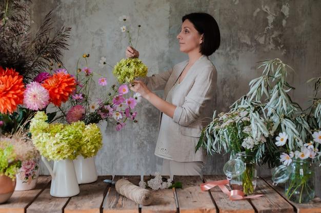 Floreria profesional femenina prepara el arreglo de flores silvestres.
