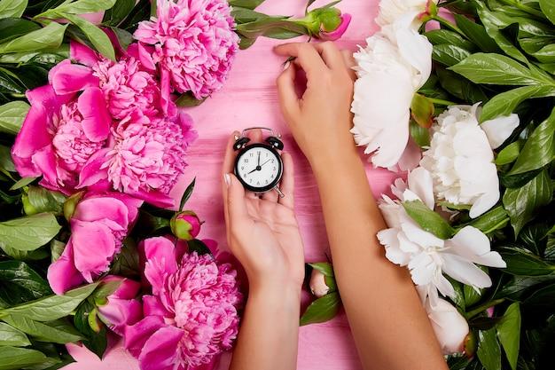Floreria en el trabajo, las manos de mujer sostienen despertador.