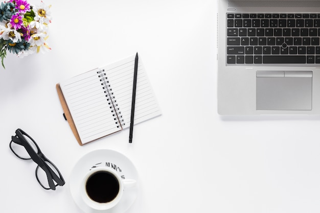 Florero; los anteojos; diario; lápiz y taza de café con ordenador portátil sobre fondo blanco