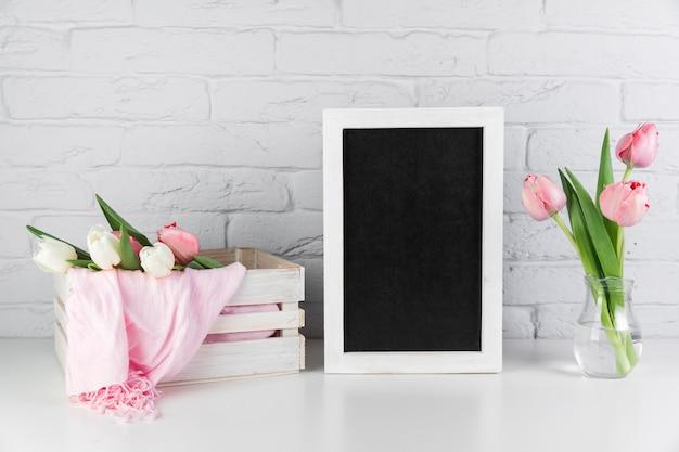 Florero y caja de tulipanes cerca del marco de borde blanco negro en blanco en el escritorio contra la pared de ladrillo