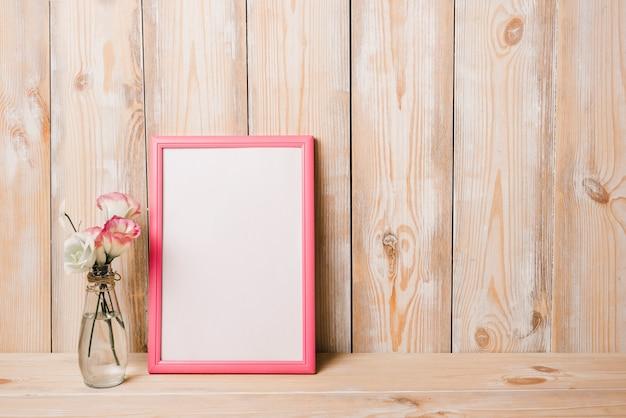 Florero cerca del marco blanco en blanco con borde rosado contra la pared de madera