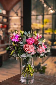 Florero con composición de flores en mesa de madera mezcla rosas