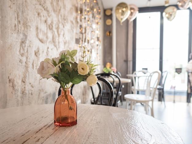 Florero con flores decorativas en mesa de madera. luz interior de la habitación