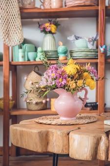 Florero con flores en una mesa de madera en la sala de estar