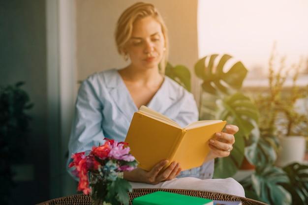 Florero en frente del libro de lectura joven hermosa mujer Foto gratis