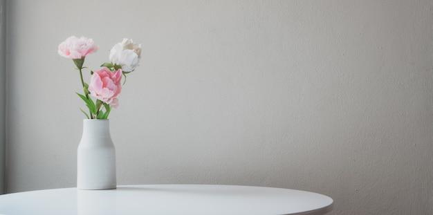 Florero fresco decoraciones en mesa blanca con espacio de copia con pared blanca