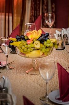 Florero con fruta en una mesa bellamente decorada en tonos rojos