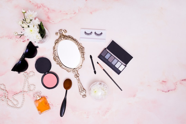 Florero; gafas de sol; collar; espejo de mano; polvos faciales compactos; brocha de maquillaje; paleta de pestañas y sombras de ojos sobre fondo rosa