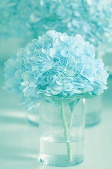 Florero con hermosas flores de hortensia azul sobre una mesa de madera. borrosa cerca de flores de hortensia azul.