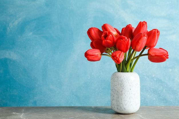 Florero con hermosos tulipanes rojos en la mesa contra azul