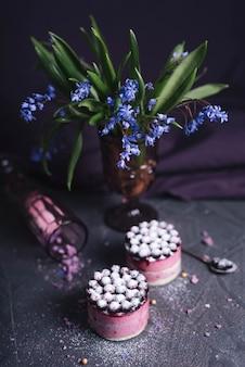 Florero púrpura con dos deliciosos pasteles de queso sobre fondo con textura de roca
