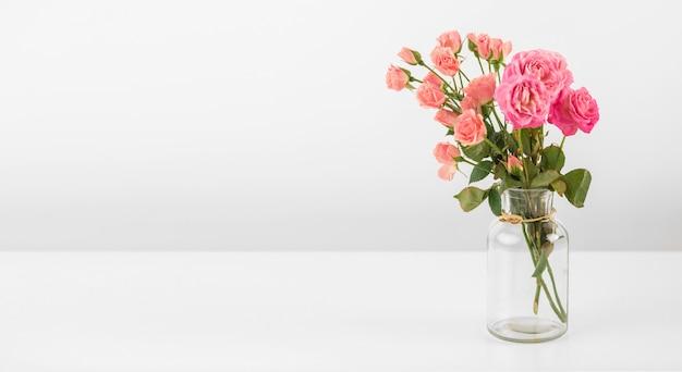 Florero con rosas en mesa
