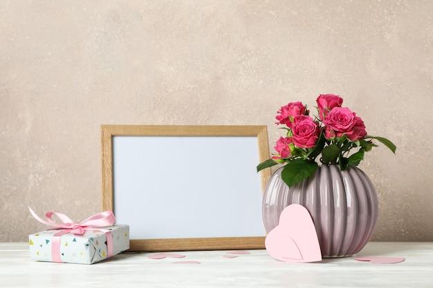 Florero con rosas rosadas, marco vacío, regalo y pequeños corazones en mesa blanca