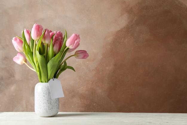 Florero con tulipanes en mesa de madera, espacio para texto