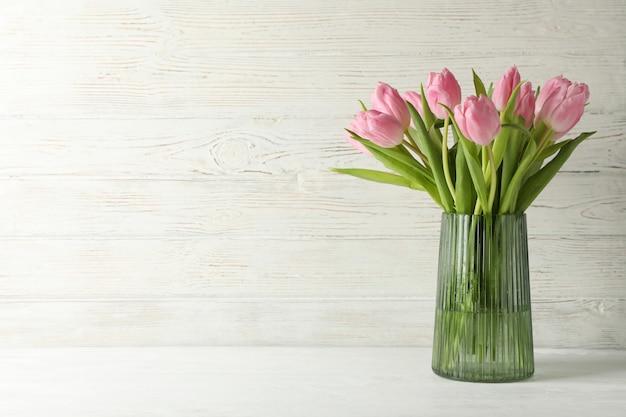Florero con tulipanes sobre fondo blanco de madera, espacio para texto