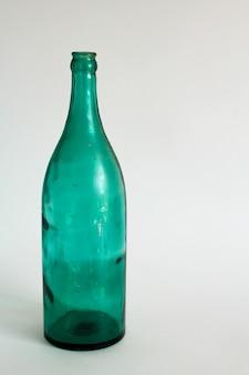 Florero verde transparente de la botella en un fondo blanco