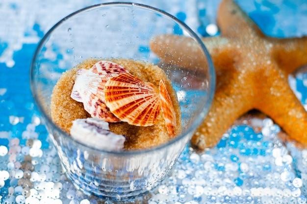 Florero de vidrio con arena dulce de azúcar morena y diferentes conchas marinas