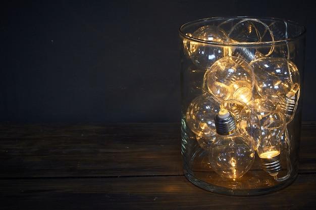 Florero de vidrio lleno de bombillas luminosas en una mesa de madera