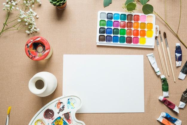 Florero y pinturas cerca de la hoja de papel